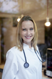 Portrait of smiling female doctor with stethoscope behind windowpane - PNEF00989