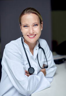Portrait of smiling female doctor with stethoscope sitting at desk - PNEF00998