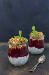 Two glasses of chia pudding with coconut milk, red fruit jelly and peanut granola topping - JUNF01358