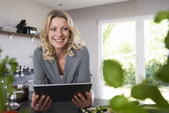 Smiling woman using tablet in kitchen - PDF01734
