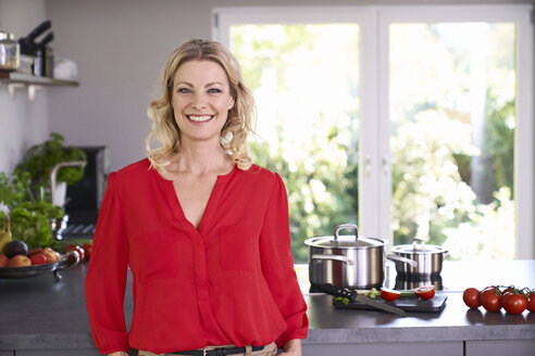Portrait of smiling woman wearing red blouse standing in kitchen - PDF01743
