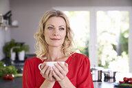Portrait of woman drinking coffee in kitchen - PDF01746