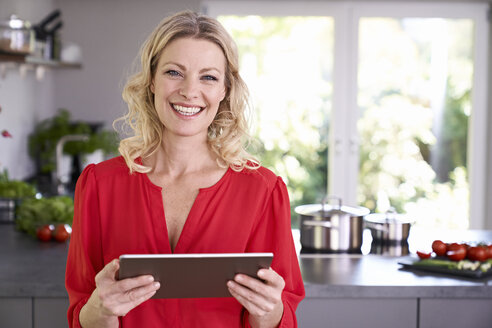 Portrait of smiling woman holding tablet in kitchen - PDF01749