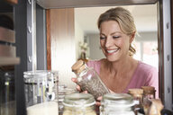 Smiling woman in kitchen taking jar from kitchen cabinet - PDF01755