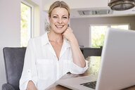 Portrait of smiling businesswoman using laptop at home - PDF01758
