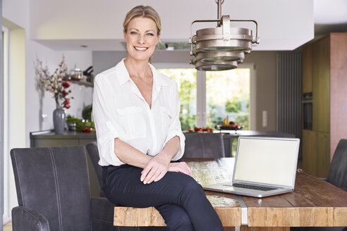 Portrait of smiling businesswoman at home sitting on table with laptop - PDF01761