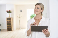 Smiling woman using tablet at home - PDF01764