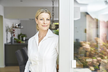 Portrait of confident woman standing at French door at home - PDF01770