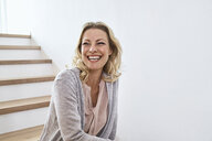 Laughing woman sitting on stairs at home - PDF01773