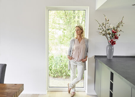 Woman standing at French door at home - PDF01776