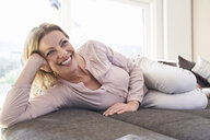 Happy woman lying on couch at home - PDF01785