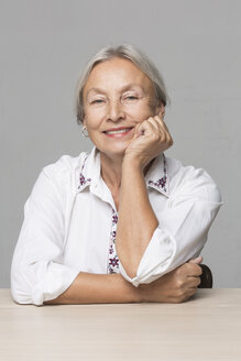 Portrait of senior woman with grey hair sitting at table with head in her hand - VGF00010