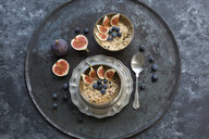 Bowls of porridge with sliced figs, blueberries and dried berries - JUNF01388