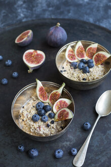 Bowls of porridge with sliced figs, blueberries and dried berries - JUNF01391