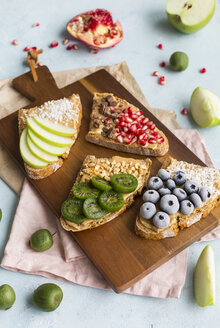 Bread slices with various toppings on wooden board - JUNF01416