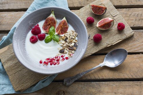 Bowl of natural yoghurt with fruit muesli, raspberries, figs and pomegranate seed - JUNF01428
