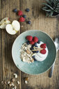 Breakfast bowl with granola, yogurt, nuts, apple, raspberry, blueberry on wood - ASF06237