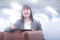 Businesswoman in office with digital tablet smiling - CUF44234