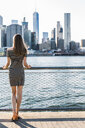 USA, New York, Brooklyn, back view of woman standing in front of East River - GIOF04552