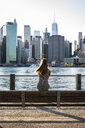 USA, New York, Brooklyn, back view of woman sitting on bench in front of East River and skyline of Manhattan - GIOF04570