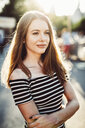 Portrait of smiling young woman wearing striped dress at sunset - GIOF04576