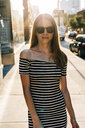 USA, New York, Brooklyn, Dumbo, portrait of smiling woman wearing striped dress and sunglasses - GIOF04588