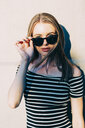 Portrait of woman wearing striped dress and sunglasses - GIOF04591