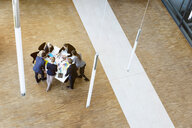 Businesswomen and men in office atrium looking at design swatches on table, high angle view - CUF44321