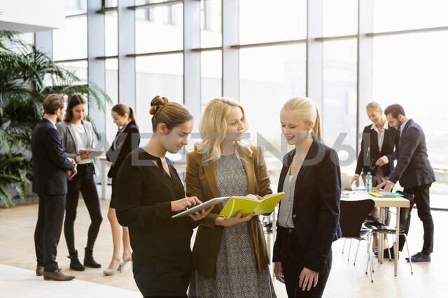 Businesswomen in office atrium using digital tablet - CUF44324 - suedhang/Westend61