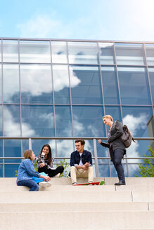 Four young adult students sitting chatting on stairway outside college - CUF44342