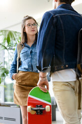 Young male and female university students chatting in university lobby - CUF44351