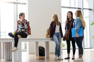 Female university students chatting together in university lobby - CUF44354