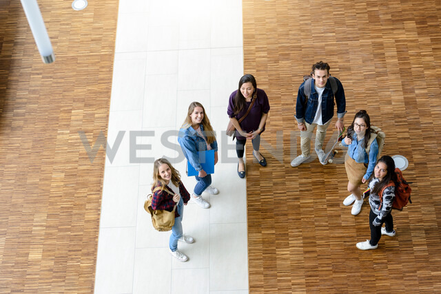 Male and female university students looking up from university lobby, high angle portrait - CUF44357