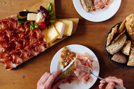 Woman eating variety of bread, cheese and parma ham at table, overhead close up of hands - CUF44423