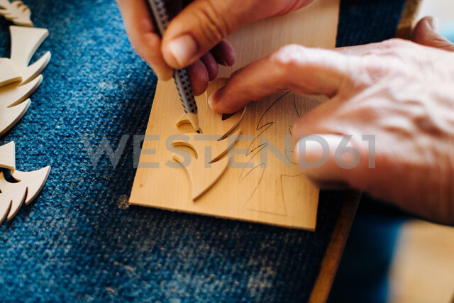 Carpenter drawing outline of wooden christmas tree, close up of hands - CUF44426