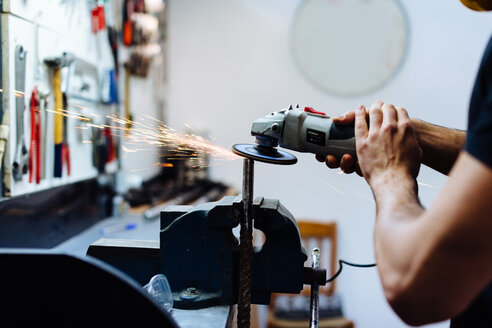 Young man using angle grinder on metal in workshop, cropped - CUF44429