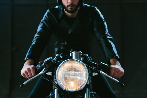 Young male motorcyclist straddling vintage motorcycle in garage, cropped front view - CUF44435