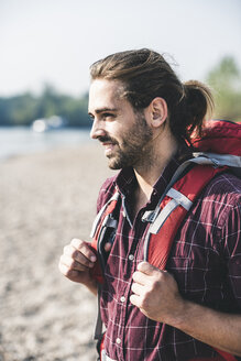 Smiling young man with backpack outdoors - UUF15313