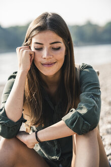 Portrait of smiling young woman sitting outdoors - UUF15319