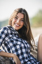Portrait of smiling young woman sitting outdoors - UUF15340