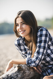 Smiling young woman sitting outdoors - UUF15343