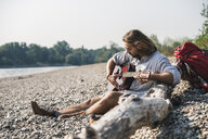 Young man sitting at the riverside playing guitar - UUF15349