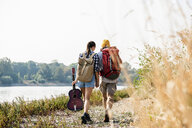 Rear view of young couple with backpacks and guitar walking at the riverside - UUF15361