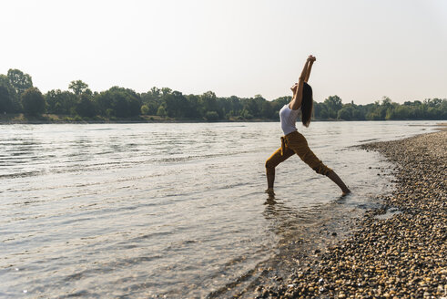 Young woman standing in water of a river practicing yoga - UUF15373