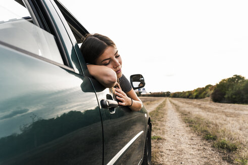 Young woman leaning out of car window on dirt track - UUF15412