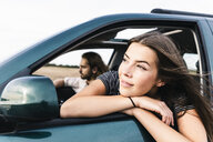 Smiling young woman leaning out of car window - UUF15415