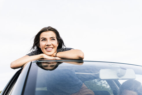 Smiling young woman looking out of sunroof of a car - UUF15418