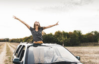 Carefree young woman looking out of sunroof of a car - UUF15421
