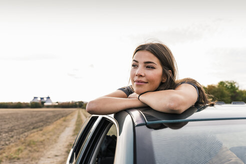 Smiling young woman looking out of sunroof of a car - UUF15424