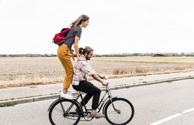 Happy young couple riding together on one bicycle on country road - UUF15445